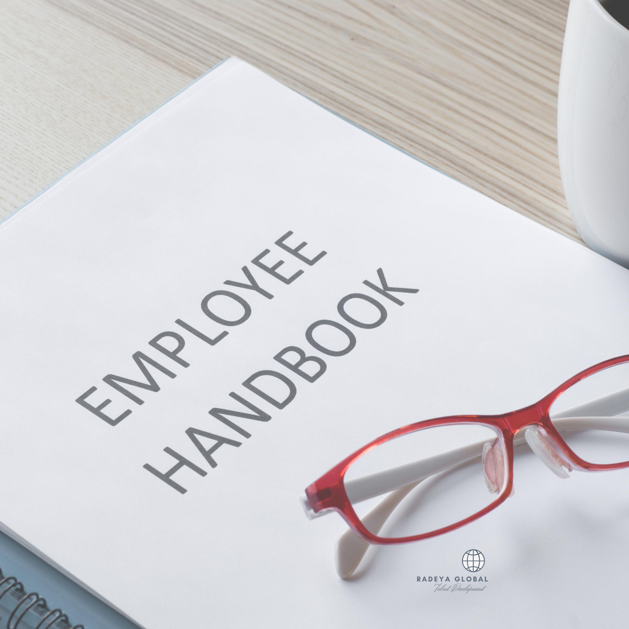 Employee handbook plus red glasses on desk